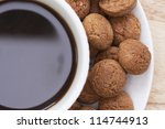 Close up of cup of coffee with kruidnootjes, Dutch spice cookies, around edge.  Shot from directly above - stock photo