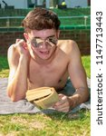 Young male adult laying in the sun reading a book - stock photo