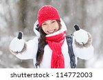 Happy young Asian woman with a beautiful vivacious smile dressed warmly in winter clothes standing outdoors in a snowstorm giving thumbs up gesture of approval - stock photo