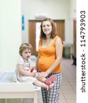 pregnant woman with child waits to attendance of doctor  at the clinic - stock photo