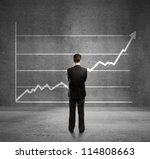businessman looks at growth chart - stock photo
