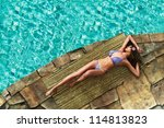 Beautiful woman sunbathing by a tropical swimming pool. - stock photo