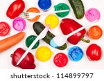 motley paints, vegetables (tomatos, cucumbers, sweet peppers, carrot) and plastic fork, knife and spoon on the white background. studio shot - stock photo