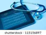 Doctor workplace with digital tablet and stethoscope. Electrocardiogram (ECG) on tablet screen. Application of modern technology in medicine concept. - stock photo
