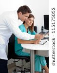 Male dentist and assistant checking X-ray at dental clinic - stock photo