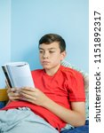 Caucasian teenage boy reading a book sitting up in bed - stock photo