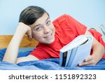 Caucasian teenage boy reading a book laying on a bed laughing - stock photo