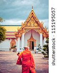 BANGKOK, THAILAND - AUGUST 03: Buddhist monk walks towards Wat Pho temple on August 03, 2012 in Bangkok. Wat Pho is one of the oldest temples in Bangkok and is home to the famous Reclining Buddah - stock photo