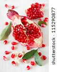 Fresh ripe pomegranate with leaves on a white board. - stock photo