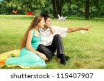 Guy shows girl the finger at something in the distance - stock photo