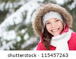 Winter woman portrait outdoors in snow forest. Smiling happy multiracial Asian / Caucasian female model blissful and content looking at camera on cold snowy winter day outside. - stock photo