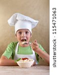 A delicious bite of traditional italian pasta - young boy eating, wearing a chef hat - stock photo