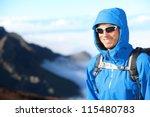 Hiker man trekking portrait in high mountain. Hiking male in alpine clothing hard shell jacket above in mountain above the clouds. Portrait of young man outdoorsman. - stock photo