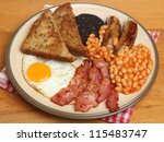 Full English cooked breakfast with bacon, sausages, egg, black pudding and baked beans. - stock photo