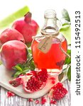 Homemade pomegranate juice and ripe pomegranates on a wooden board. - stock photo