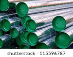 Close up of pile of metal pipes with raindrops - stock photo