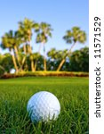 golf ball on fairway of lovely tropical golf course with dew in grass and clear blue sky - stock photo