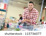 man with shopping cart with food produces in supermarket - stock photo