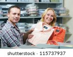 Young couple choosing business shirt during clothing shopping at sales store - stock photo