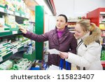 Two woman choosing bio food produces in dairy supermarket with shopping list - stock photo