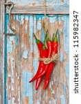 Fresh ripe chili handing with rope on an old blue board. - stock photo