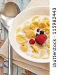 Cornflakes with fresh berries and milk. - stock photo