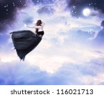 Girl in beautiful black dress jumping in the moonlight sky (serenity) - stock photo