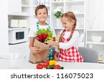 Kids unpacking the groceries in the kitchen - making fresh vegetables salad - stock photo