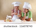 Kids with chef hats preparing the cake dough - mixing ingredients - stock photo