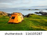 Orange camping tent on a shore in a morning light - stock photo
