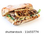 Steak sandwich.  Beef steak on a toasted baguette bread roll, with goat's cheese, spinach, and grilled onion.  Delicious! - stock photo