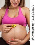 Pregnant Woman plays with a tinny little toy car over her belly - stock photo