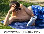 Teenage boy reading a book while sunbathing in a garden wearing sunglasses - stock photo