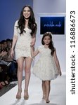 NEW YORK - OCTOBER 20: Designer Winnie & girl walk runway for petite Parade show by Mischka Aoki during kids fashion week NYC sponsored by Vogue Bambini at Industria Superstudio on Oct 20, 2012 in NYC - stock photo