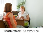Mature doctor examining the pregnant woman in clinic - stock photo