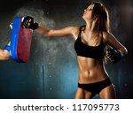 Young sexy woman hitting punching bag. - stock photo