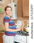 pregnant woman cooking food in her kitchen - stock photo