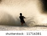 Silhouette of a barefoot water skier with backlit water spray - stock photo