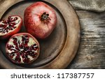 Pomegranate in rustic wooden plate - stock photo