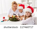 Making an advent wreath with the kids - dressed for the christmas - stock photo