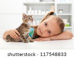 Little girl with her kitten - getting to know each other - stock photo