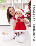 Baby girl and mother celebrating christmas together - stock photo