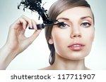 cute woman with mascara brush and black splash - stock photo