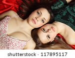 Two beautiful sexy young woman lying on her back - stock photo