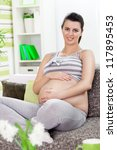 Smiling pregnant woman expecting baby - stock photo