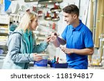 Assistant seller help buyer by demonstrating paint roller for painting at hardware store - stock photo