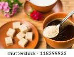 tablespoon with brown sugar on coffee cup - stock photo