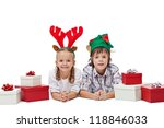 Happy kids wearing elf and reindeer hats laying with presents - the magic of christmas, isolated - stock photo