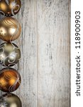 Row of golden Christmas balls with festive designs on wooden background - stock photo