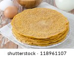 Stack of crepes made ??of corn flour on a plate and baking ingredients (eggs, flour, milk) - stock photo
